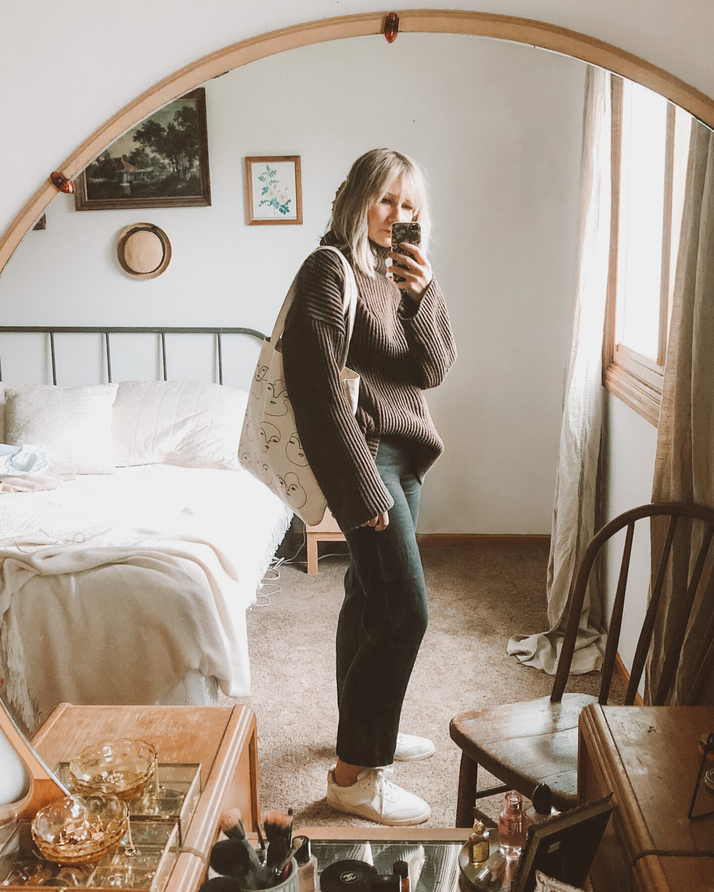 Fall Transitional Dressing: oversized brown turtleneck sweater paired with black linen pants, everlane tread sneakers, and a canvas tote bag
