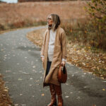 3 Cozy Outfits for Thanksgiving, camel duster maxi cardigan, taupe turtleneck sweater, blue skinny jeans, brownknee high croc effect boots, staud moon bag