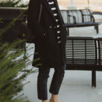 karin emily style. classic stripes, breton stripe sweater, j. crew wool coat, everlane 90's cheeky jean, washed black jeans, cap toe flats, black madewell bag, monogram necklace, oversized black sunglasses, blonde hair with bangs