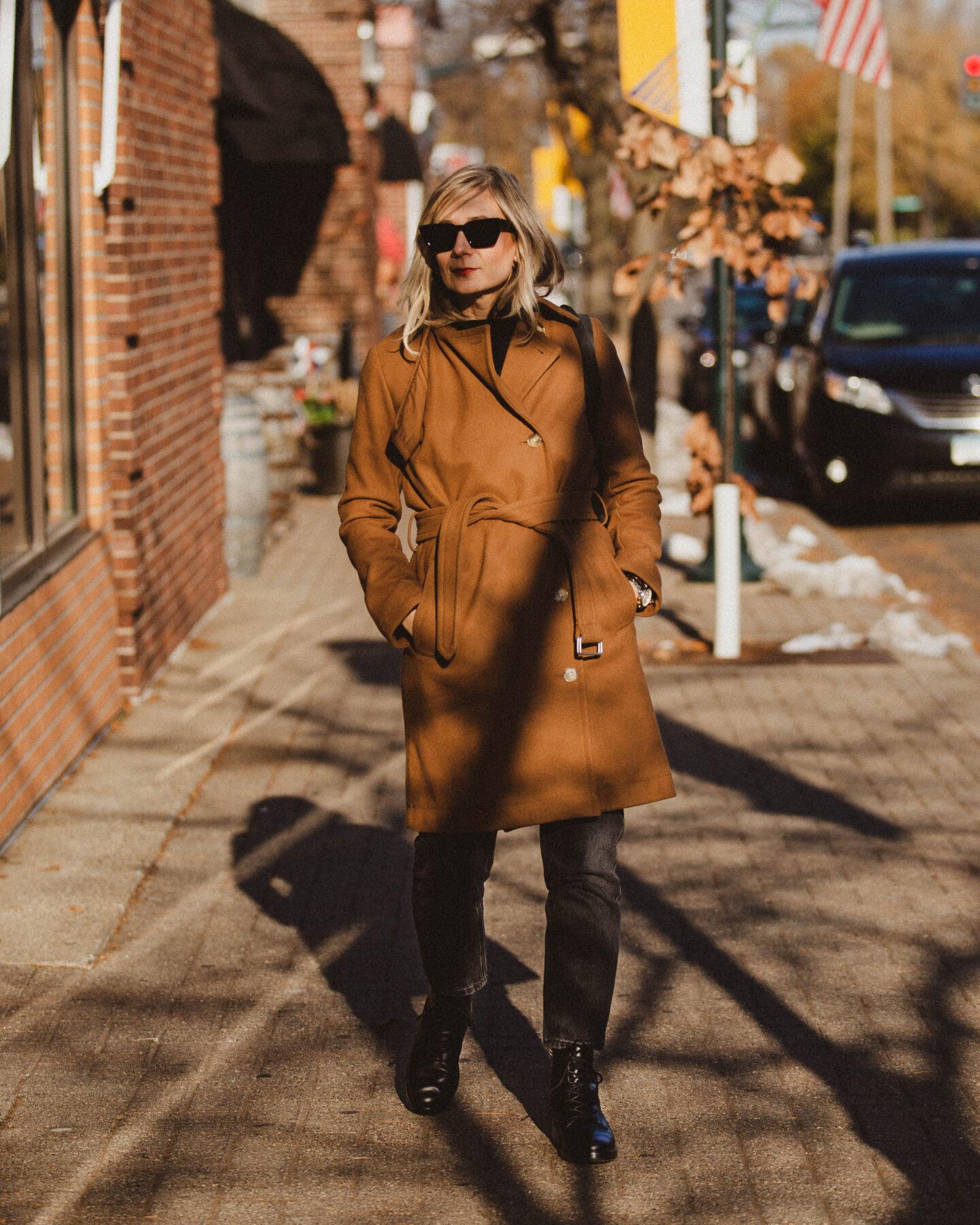 Karin Emily Style. Camel Coat, Washed Black Straight Leg Jeans, Lace Up Boots, Black Cat Eye Sunglasses