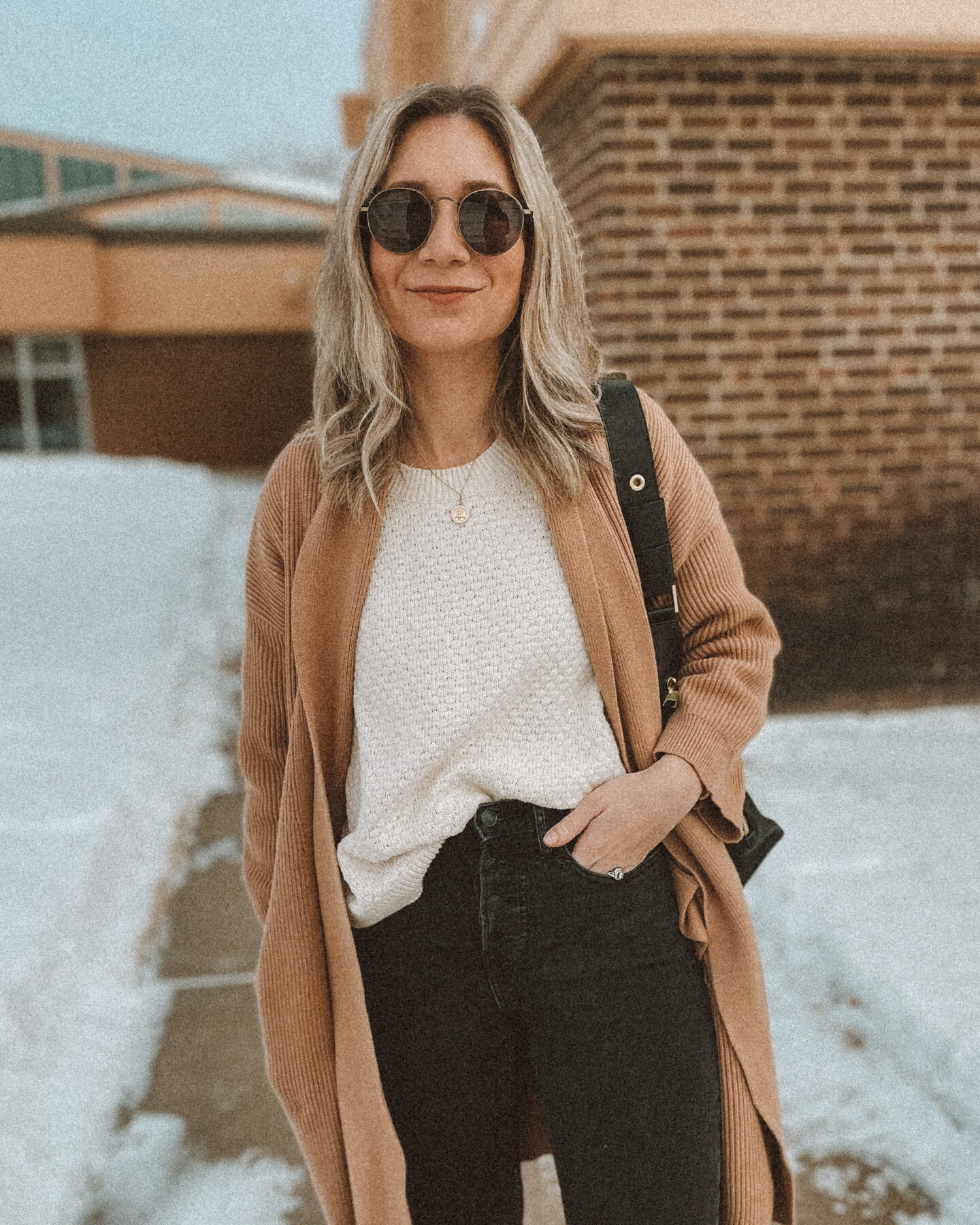cream sweater, black leather back pack, gray skinny jeans, cream sweater