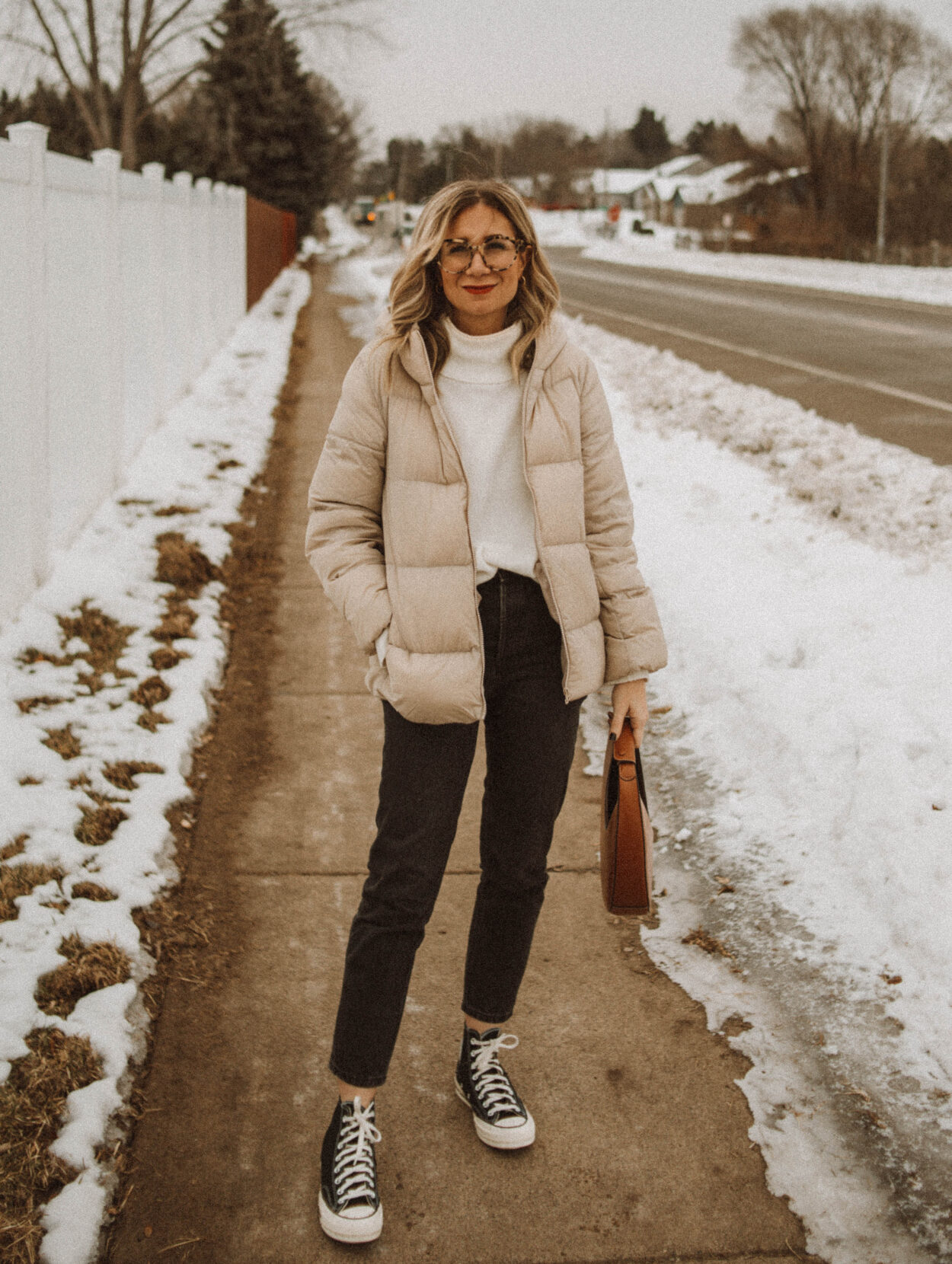 cream puffer coat, white turtleneck sweater, washed black jeans, black high top converse, staud moon bag