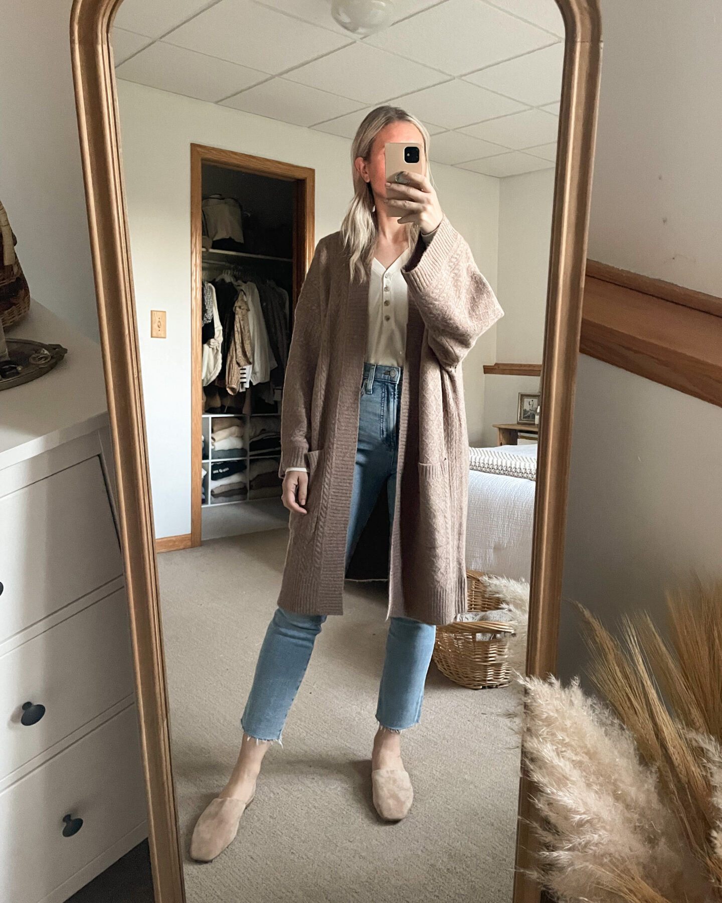 Karin Emily wears an oversized camel cardigan, light wash distressed jeans, and nude mules