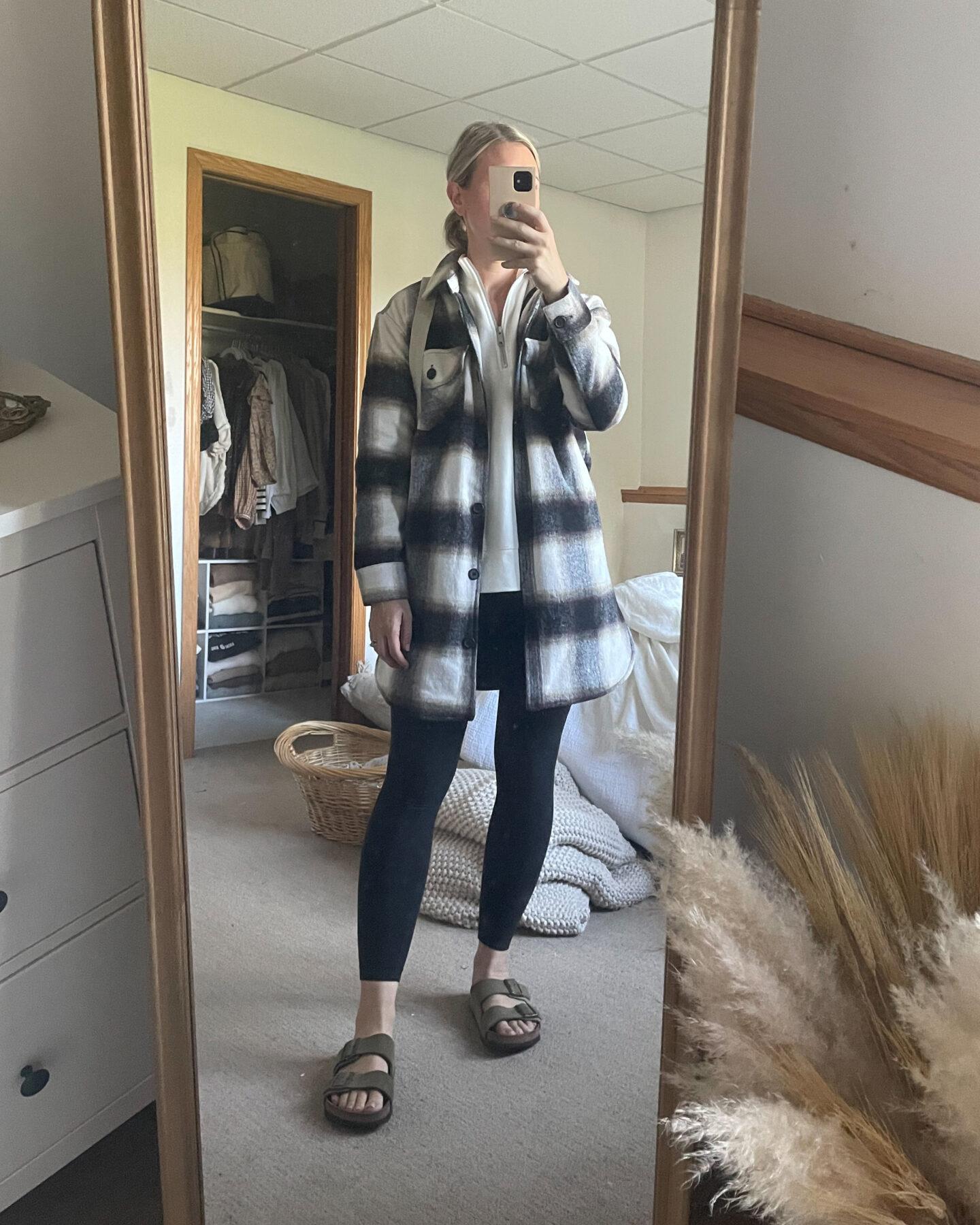 Karin Emily wears a plaid shacket, lululemon align leggings, and birkenstock arizona sandals, and a white half zip sweatshirt