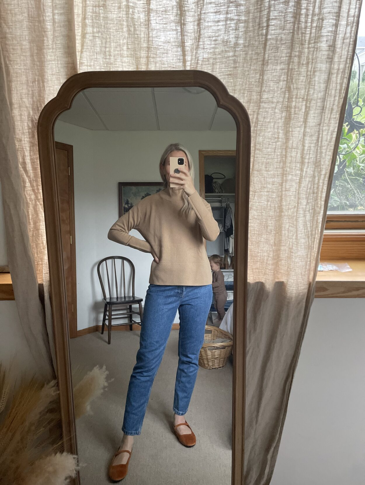 Karin Emily wears a cashmere camel colored turtleneck from Everlane