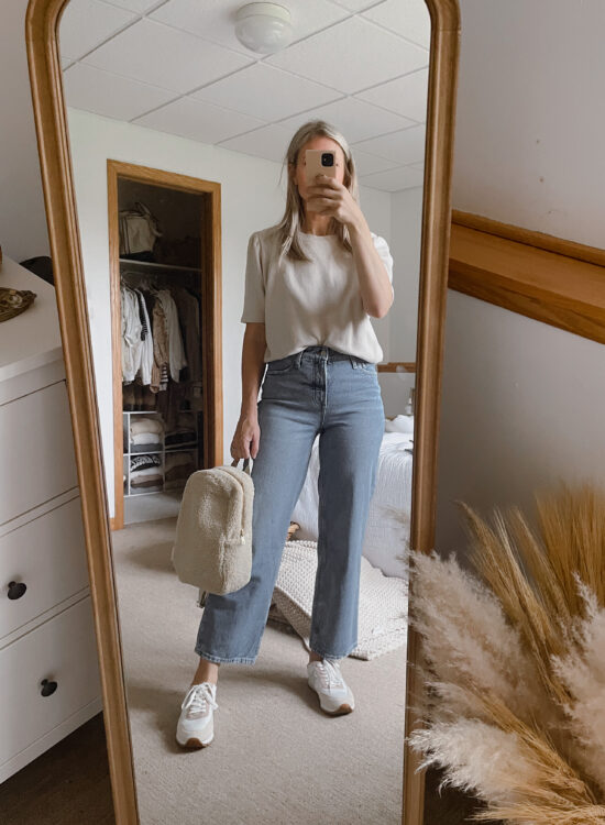 Karin Emily wears a puff sleeve sweatshirt from it is well L.A., a pair of wide leg jeans from Walmart, a sherpa backpack from studio noos, and a pair of J. Crew Sneakers