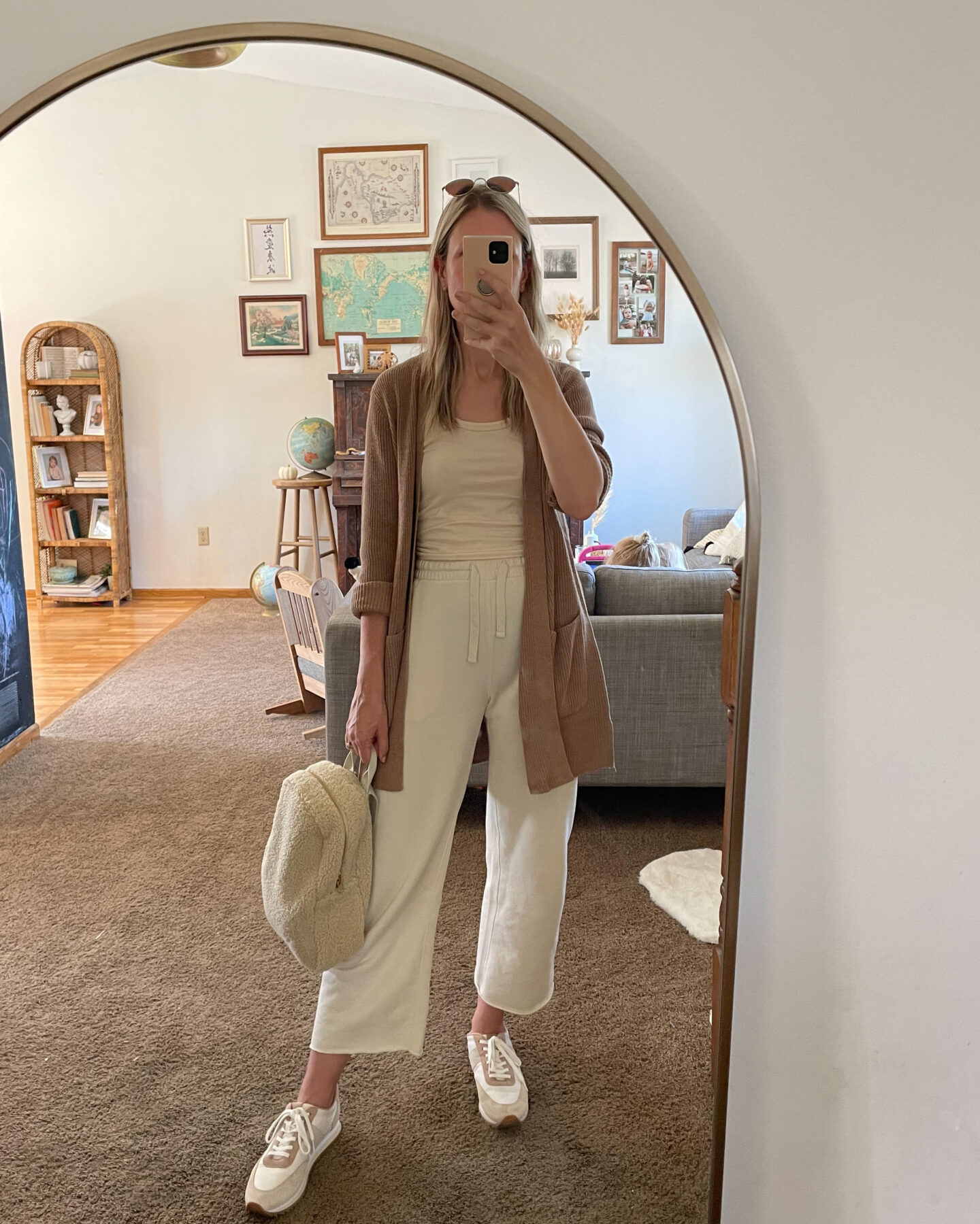Karin Emily wears a cream loungewear set with a camel cardigan on top, a pair of sneakers and a sherpa bag