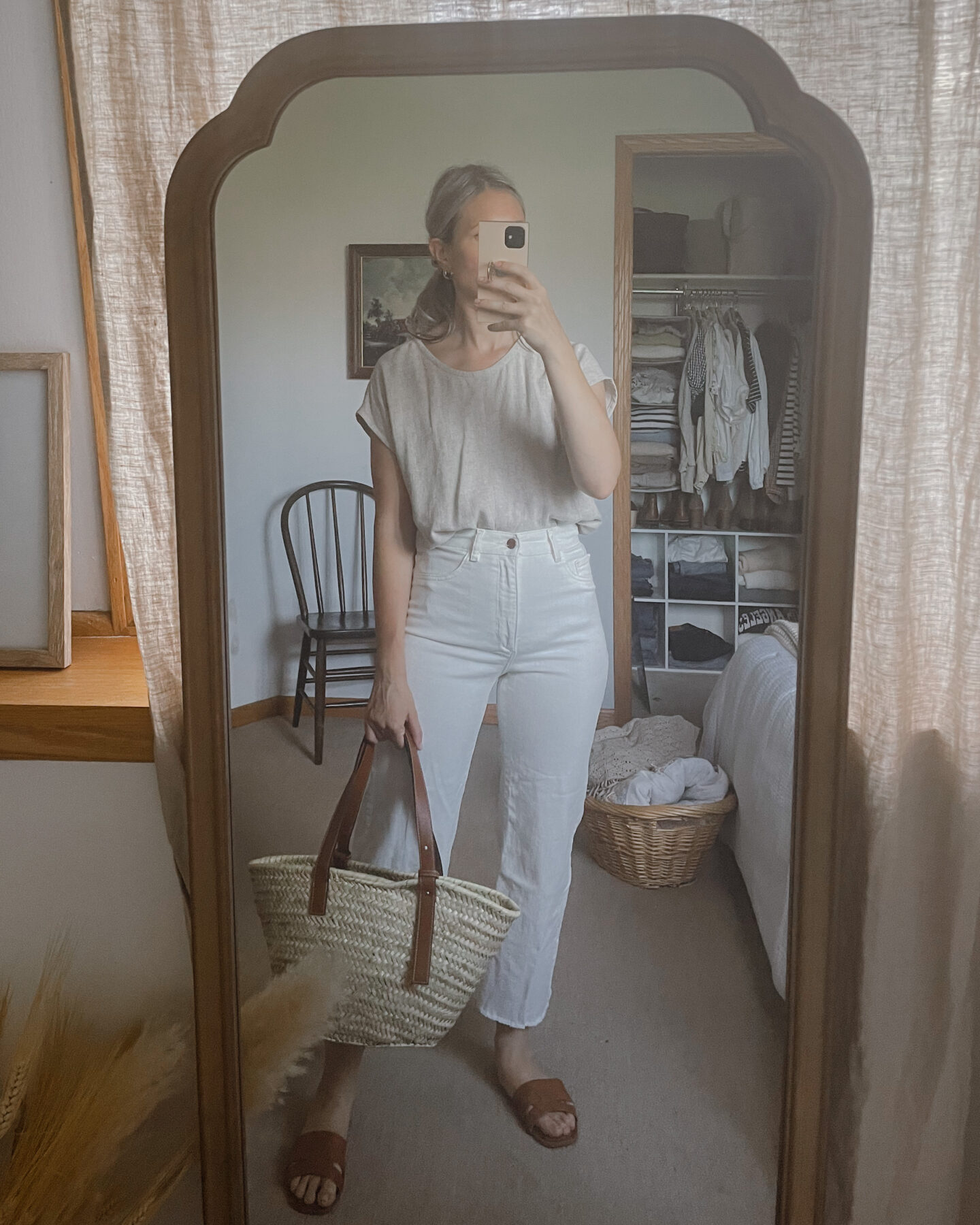 Karin Emily wears a tan shirt tucked into white wide leg jeans, brown slide sandals and a basket bag