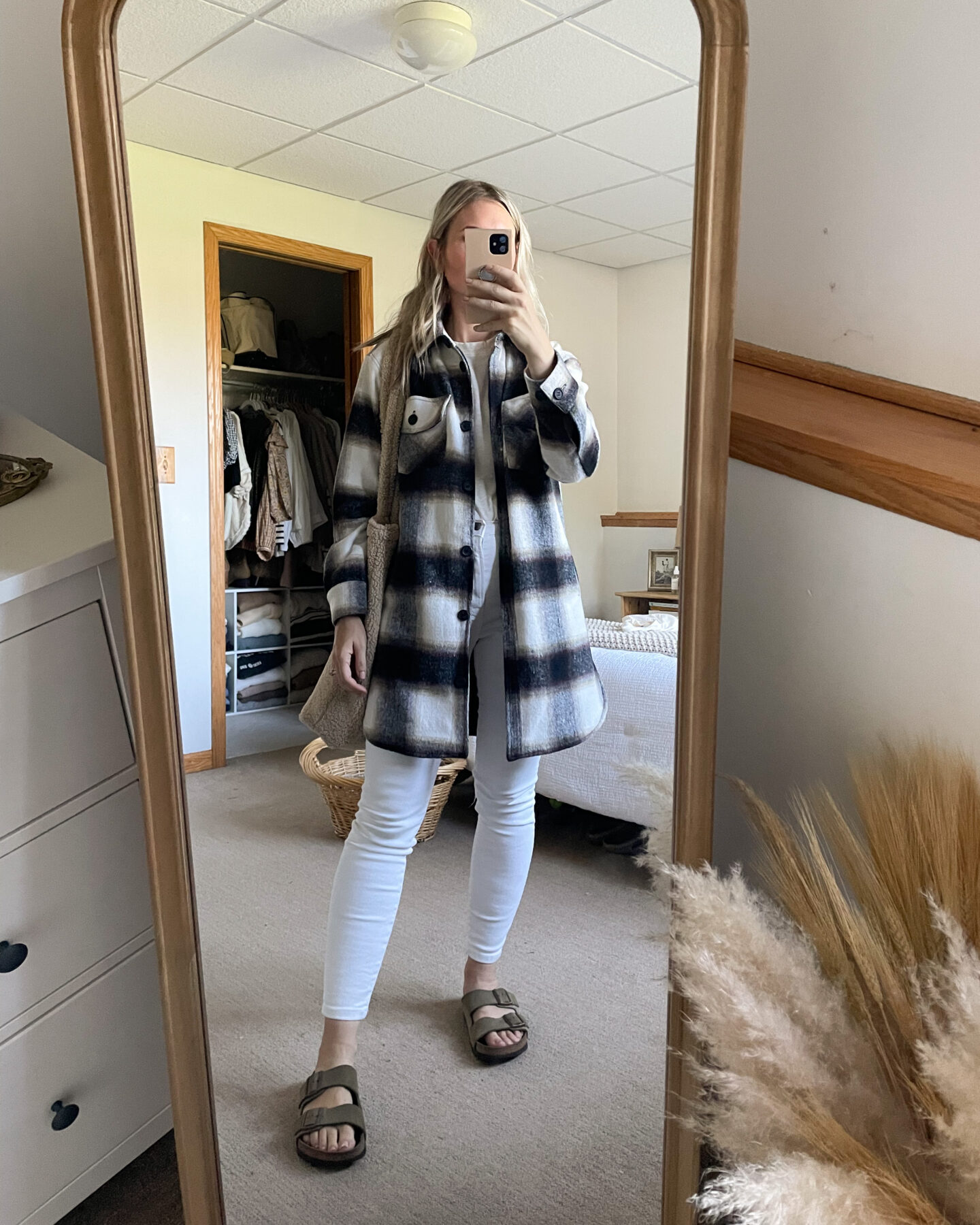 Karin Emily wears a plaid shacket over white skinny jeans and birkenstock arizonas