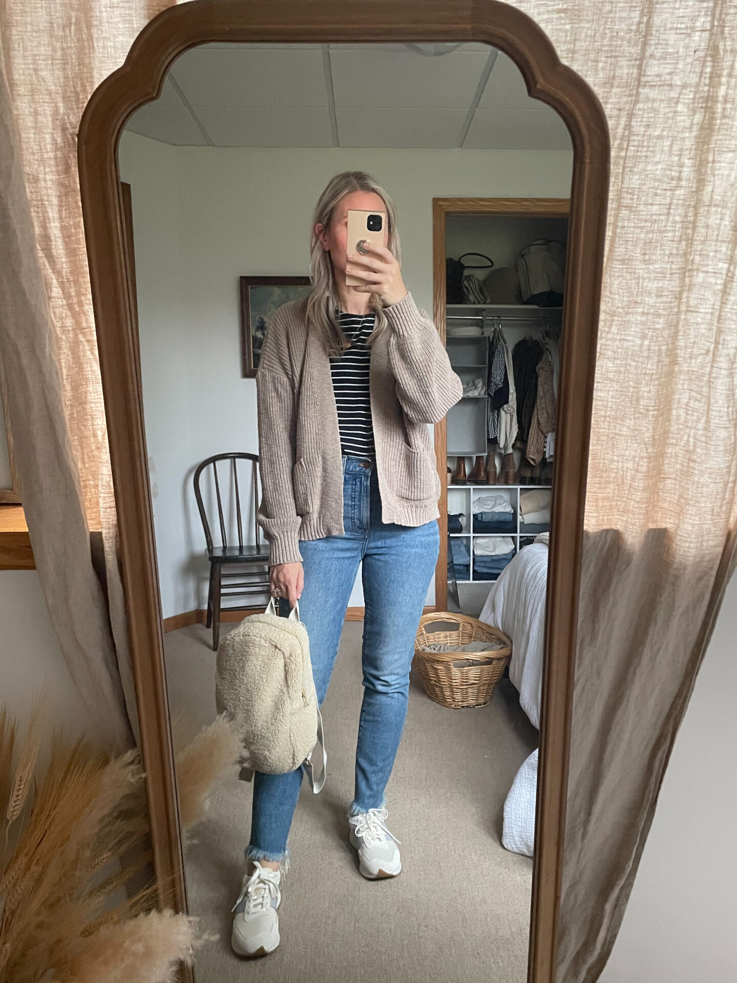 Karin Emily wears a sustainably made cardigan, striped tee, perfect vintage jeans from madewell, new balance sneakers, and a sherpa bag