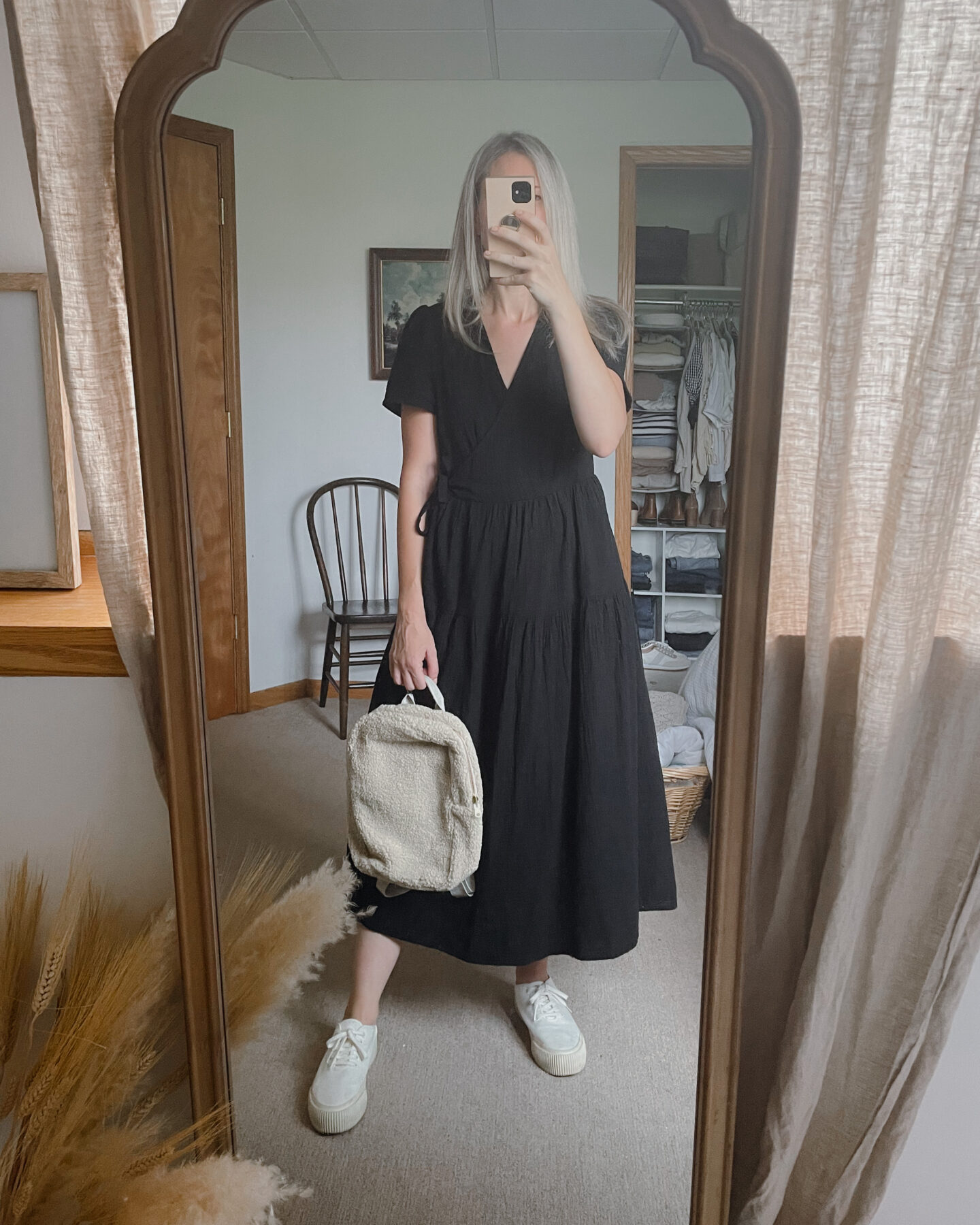 Karin Emily wears a black gauze dress with a sherpa bag and platform sneakers