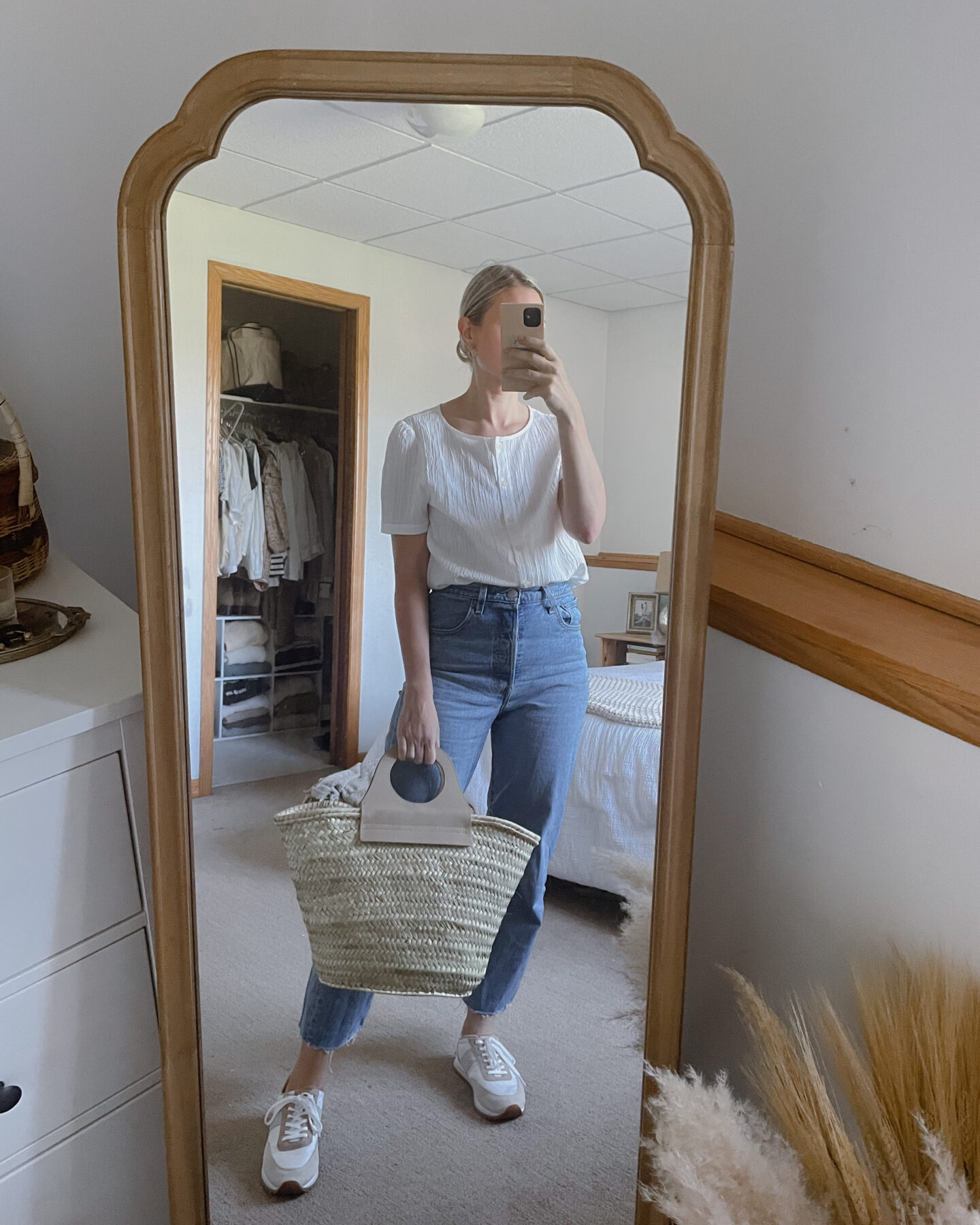 Karin Emily wears a simple white blouse with a pair of ribcage Levi's, a pair of sneakers and a Hereu basket bag