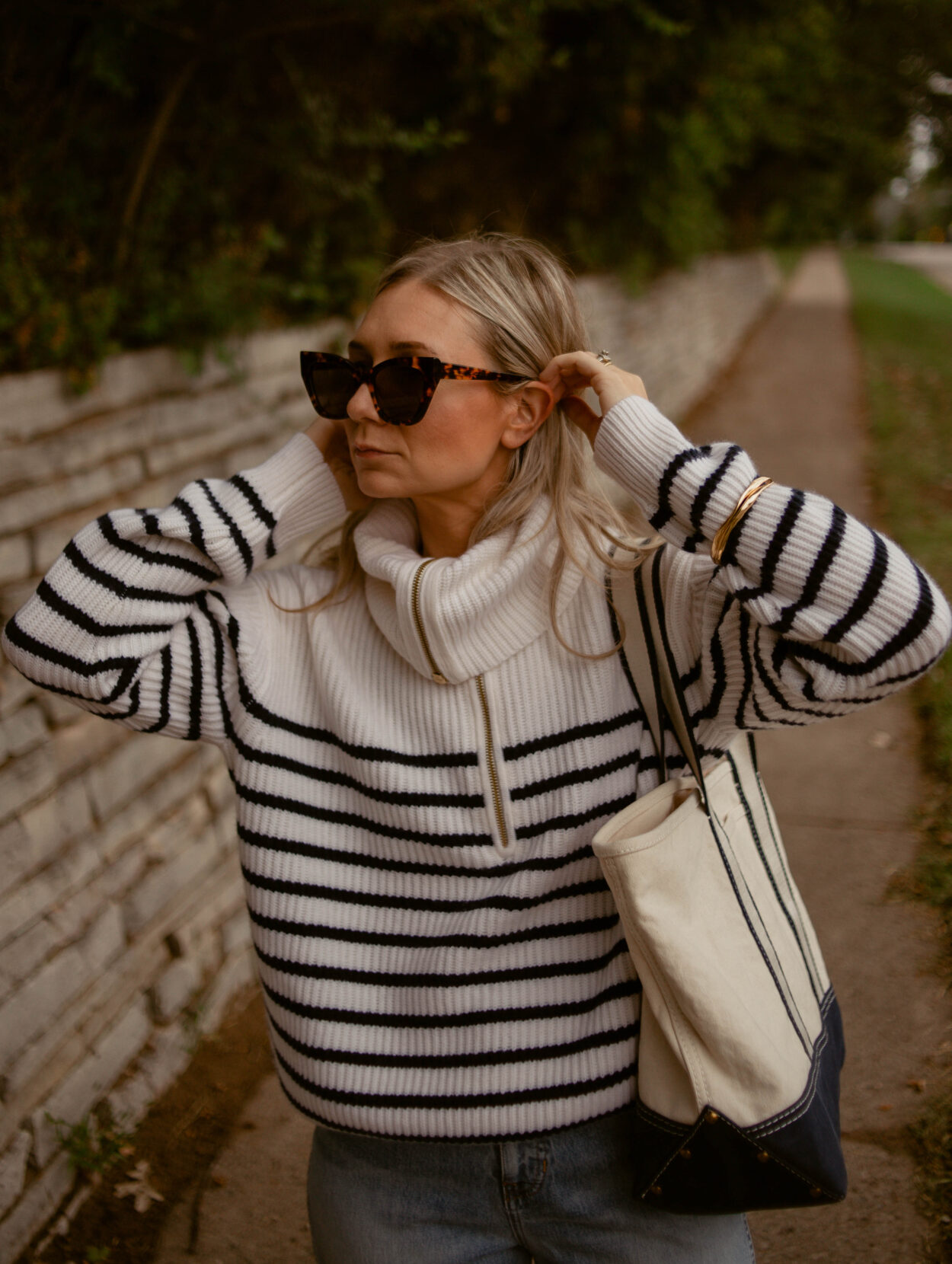 Karin Emily Wears a cashmere breton stripe sweater, light wash relaxed jeans, and sherpa mules - all from J. Crew