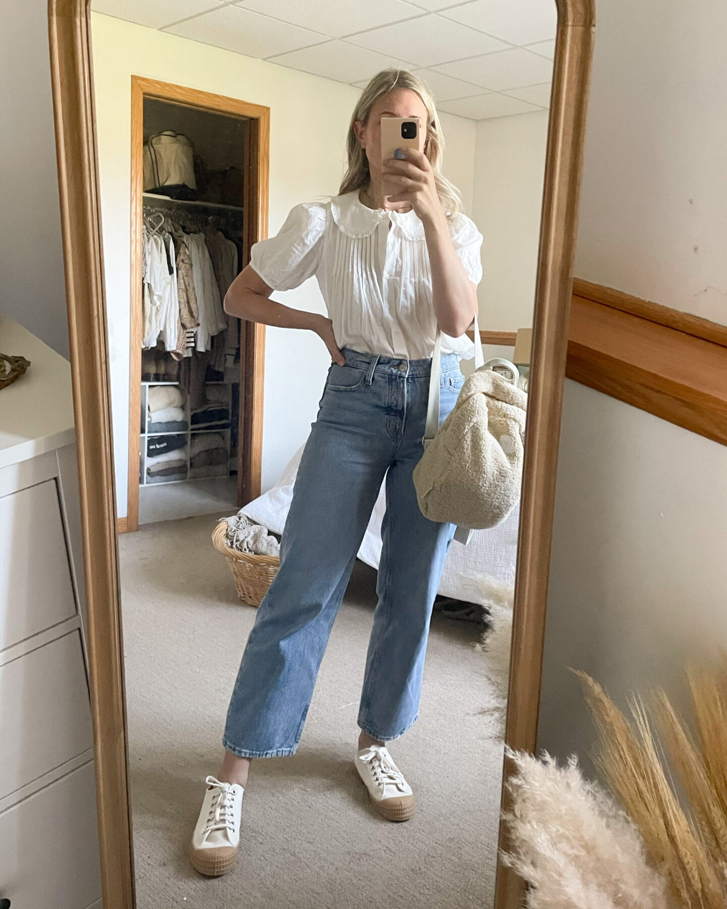 Karin Emily wears a puff sleeve blouse tucked into wide leg jeans with a sherpa backpack and canvas sneakers