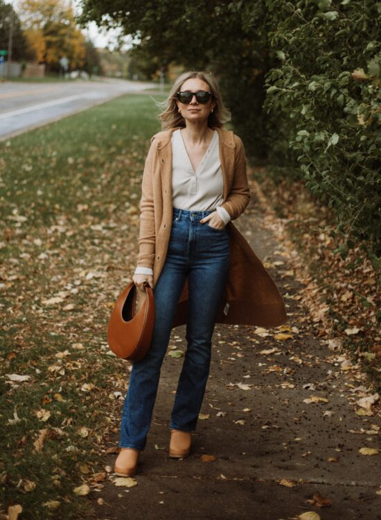 Karin Emily wears a henley tee, a long maxi cardigan from Everlane, boot leg sustainable jeans from Revolve, clogs, and a staud moon bag
