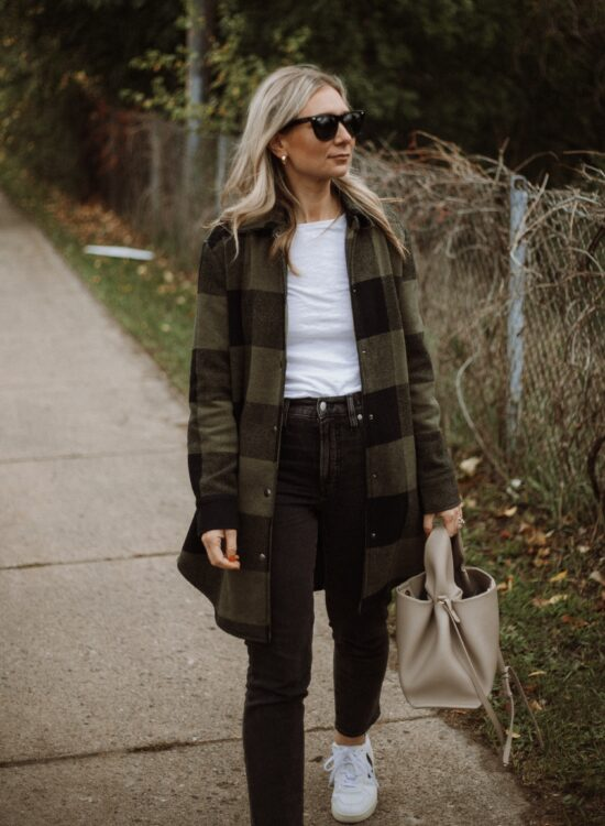 Karin Emily wears a white tee, plaid shacket, washed black perfect vintage jeans from Madewell and Veja V-10 Sneakers