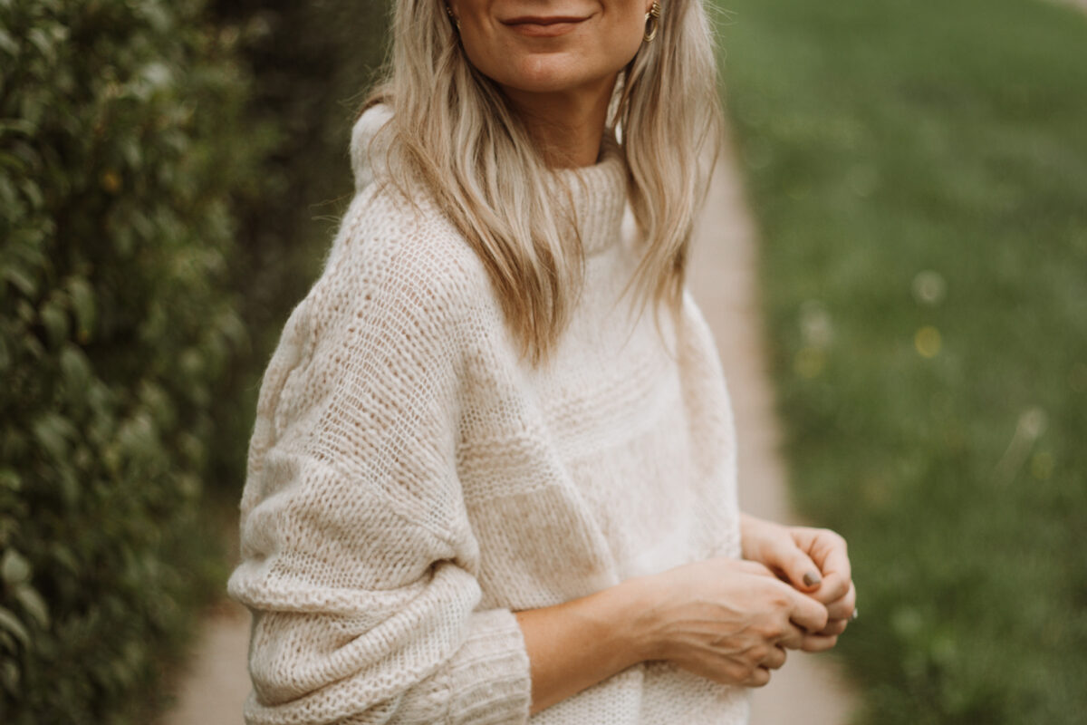 Karin Emily wears the Everlane puff sweater, light wash 90's cheeky jeans
