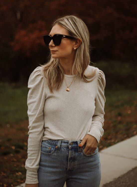 Karin Emily wear a puff sleeve top, light wash wedgie icon Levi jeans and le specs black air heart sunglasses