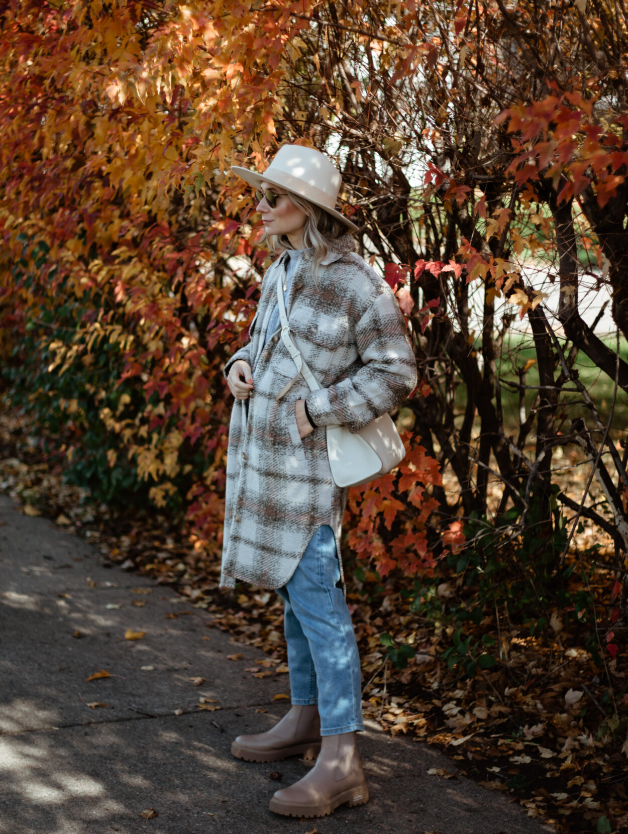 Karin Emily wears a plaid shacket, light wash jeans, a cream hat, and tan lug boots