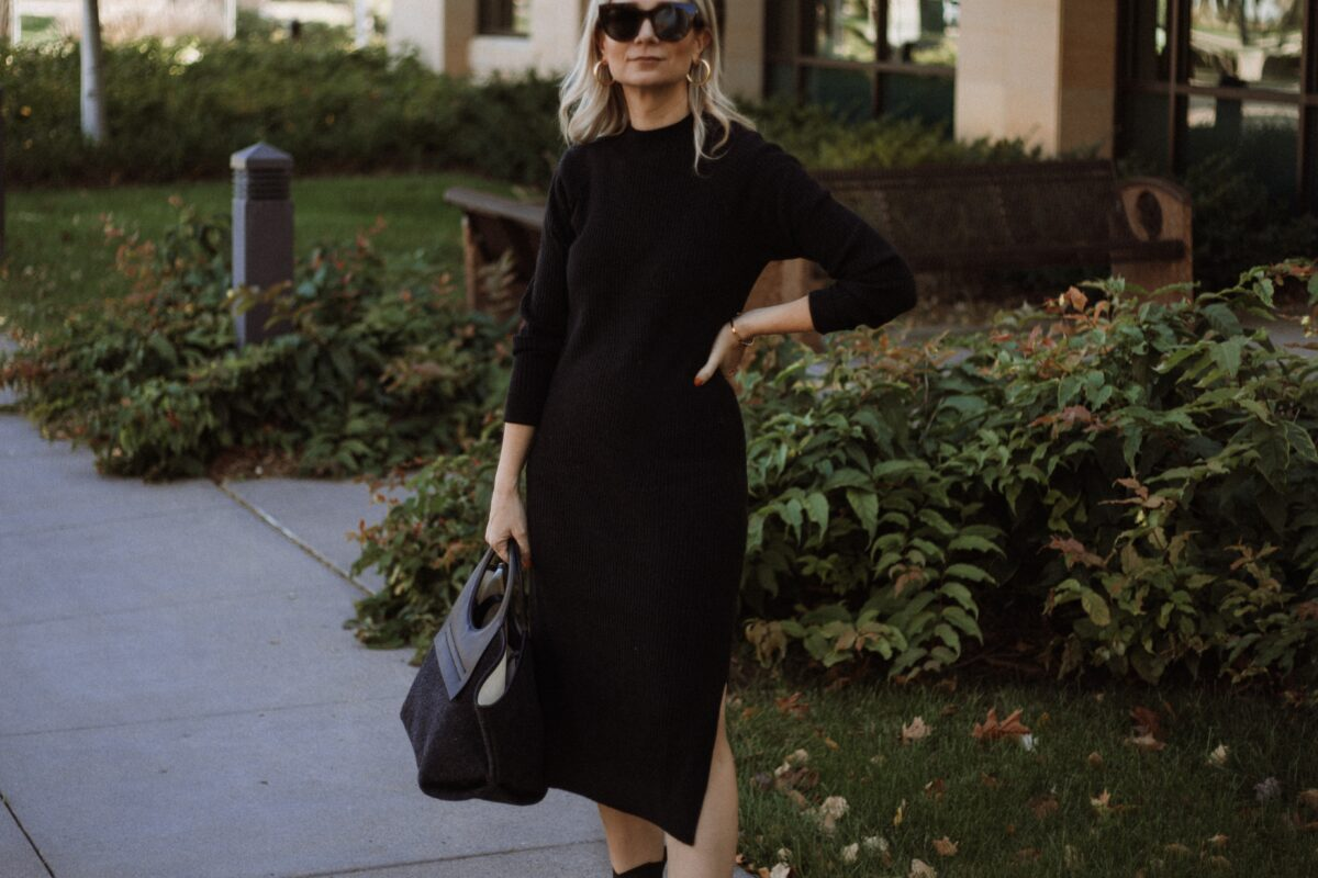 Karin Emily wears a black sweater dress, hereu bag, black cowboy boots, and oversized black sunglasses