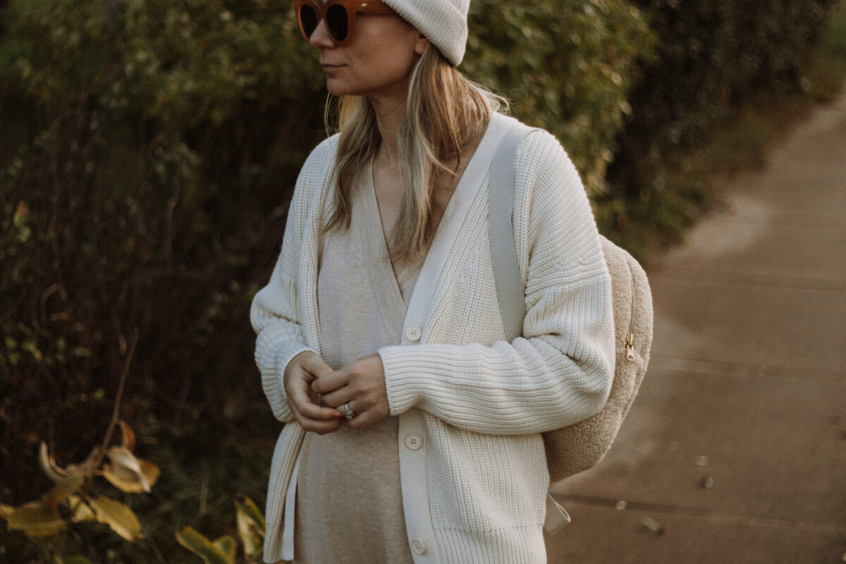 Karin Emily wears the Tradlands Shelter Cardigan, a J Crew Wool Jumpsuit and Sneakers and a Sherpa Backpack