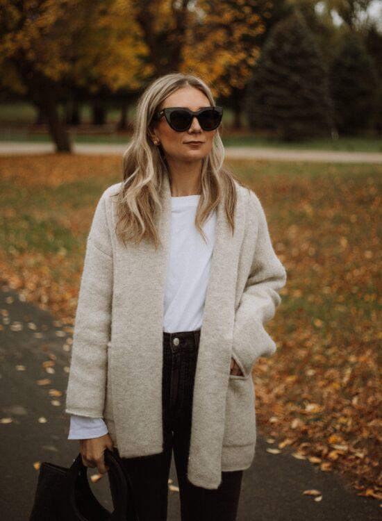 Karin Emily wears a Madewell shawl cardigan, white tee, black madewell perfect vintage jeans, and a wool Hereu bag,