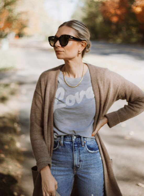 Karin Emily wears a graphic tee, cashmere cardigan, and distressed jeans